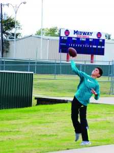 Seventh Grader Jake Ratcliff plays quarterback for GPA. Here he plays a game of pick-up behind the bleachers at the varsity state game.